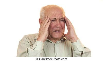 Senior man having a headache rubbing his temples