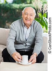 Senior Man Having Coffee At Nursing Home Porch - Portrait of...