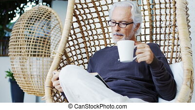 Senior man having coffee while reading a book 4k