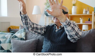 Senior man is having fun with augmented reality glasses wearing headset moving hands sitting on sofa at home. Entertainment and modern devices concept.