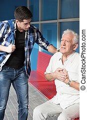 Senior man having heart infarct at the bus stop