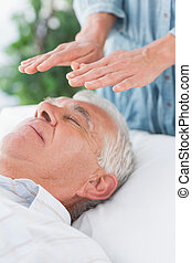 Senior man having Reiki treatment