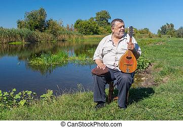Senior man having rest on a riverside sitting on a wicker stool