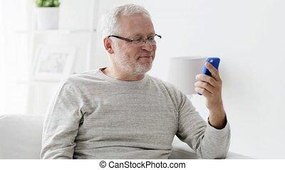 senior man having video call on smartphone at home