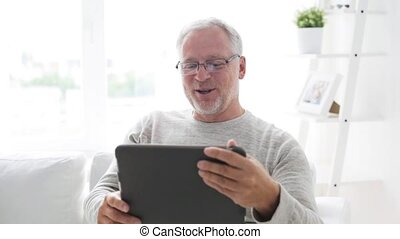 senior man having video call on tablet pc at home 117
