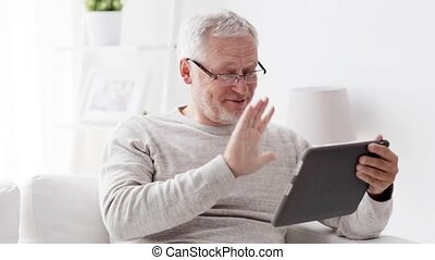 senior man having video call on tablet pc at home