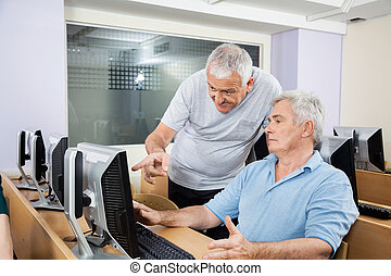 Senior Man Helping Classmate In Using Computer