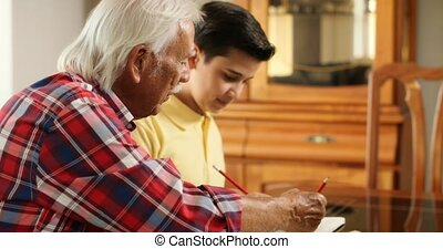 Senior Man Helping Grandson With School Homework At Home -...