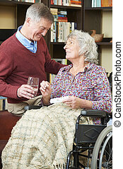 Senior Man Helping Wife In Wheelchair With Medication
