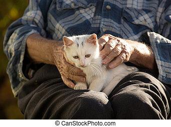 Senior man holding cat in lap