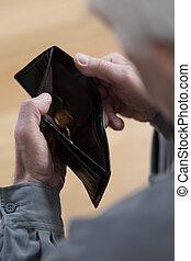 Senior man holding empty wallet