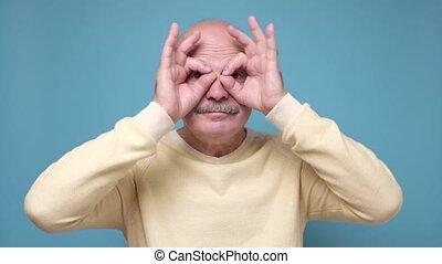 Senior man holding fingers near eyes like glasses or mask like super hero. I need new glasses concept