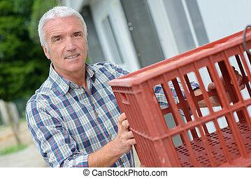 Senior man holding plastic crate