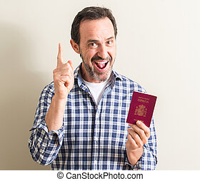 Senior man holding spanish passport surprised with an idea or question pointing finger with happy face, number one