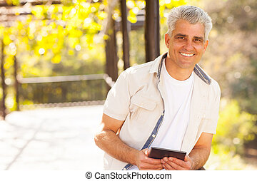 senior man holding tablet computer outdoors