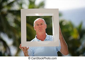 Senior man holding up a square frame