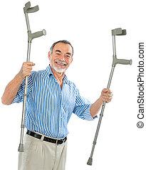 senior man holds the crutches