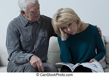Senior man hugging upset wife having financial problems