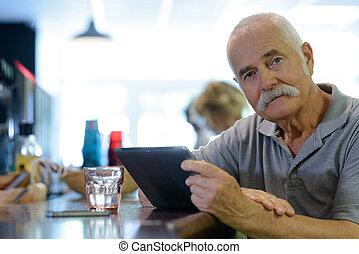 senior man in a bar alone