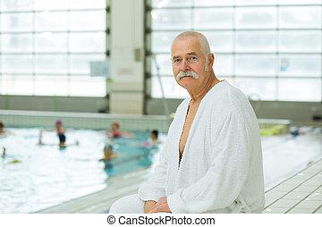senior man in a bathrobe standing in the spa
