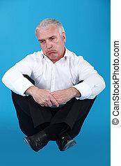 senior man in a suit looking sad