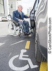senior man in a wheelchair going in a car