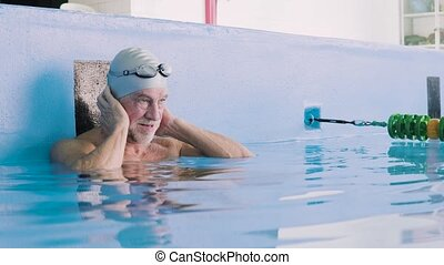 Senior man in an indoor swimming pool. Active pensioner...