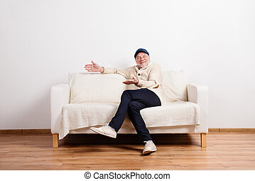 Senior man in beige sweater sitting on sofa, studio shot.