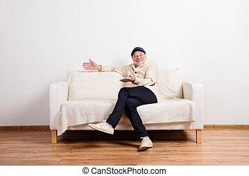 Senior man in beige sweater sitting on sofa, studio shot.