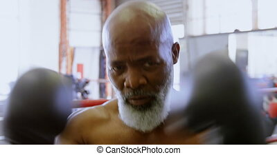 Senior man in black boxing gloves 4k - Close- up of senior...
