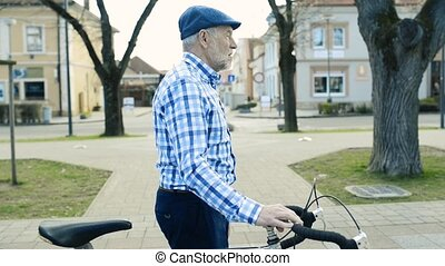 Senior man in blue checked shirt with bicycle in town. -...