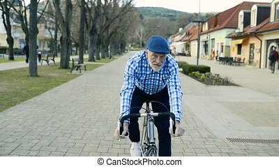 Senior man in blue shirt riding a bicycle in town.