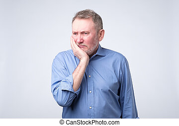 Senior man in blue shirt suffering tooth pain