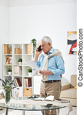 Senior man in casualwear looking through papers and talking on smartphone