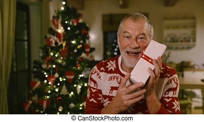 Senior man in front of Christmas tree holding gift.