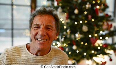 Senior man in front of illuminated Christmas tree. - Senior...