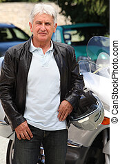 Senior man in front of motorcycle