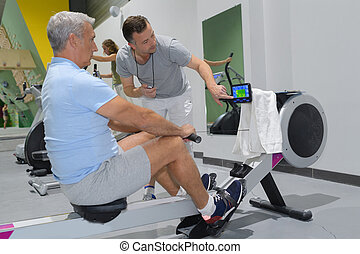 senior man in gym using a rowing machine