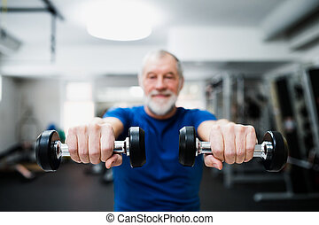 Senior man in gym working out with weights.