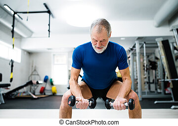 Senior man in gym working out with weights, squatting.