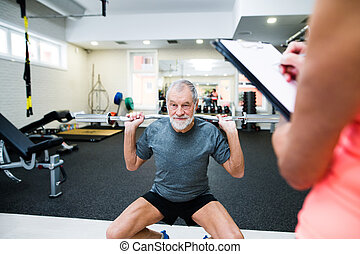 Senior man in gym working out with weights