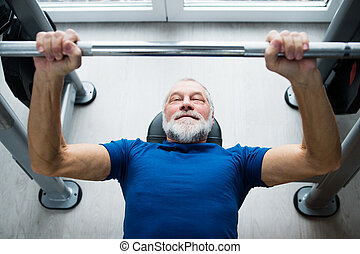 Senior man in gym working out with weights, bench pressing...