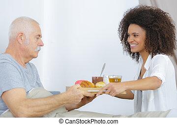 senior man in nursing home having breakfast in bed