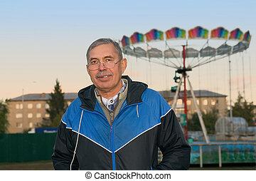 Senior man in park near chilldren playground