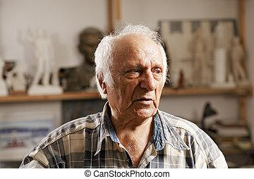 Senior man in sculptors workshop