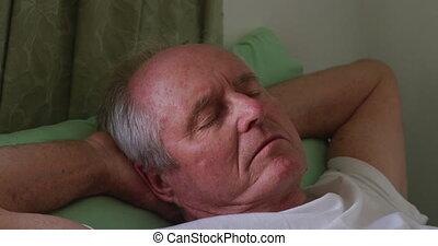 Senior man in social distancing sleeping in retirement house...