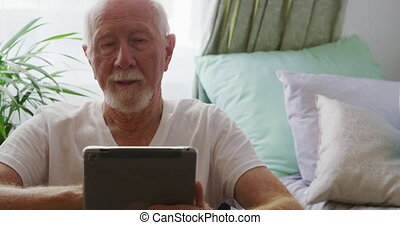 Senior man in social distancing using digital tablet