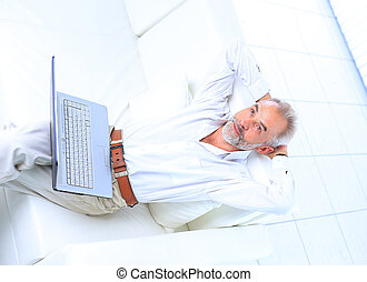 Senior man in sofa with laptop