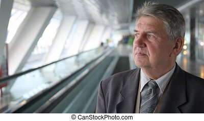senior man in suit moving up on escalator - Senior man in...