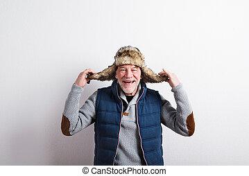 Senior man in sweater, vest jacket and fur hat, studio shot.